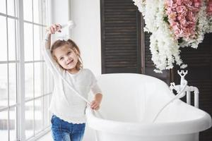 Funny little baby girl with curly hair. Get ready to take a bath. Spacious lighted bathroom. The concept of a healthy and clean body. Caring for yourself since childhood photo