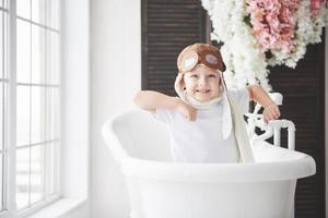 Happy kid in pilot hat playing in bathroom. Childhood. Fantasy, imagination. photo