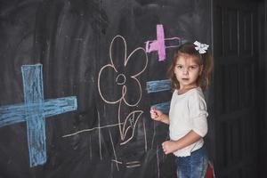 Curly little baby girl drawing with crayon color on the wall. Works of child. Cute pupil writing on chalkboard photo