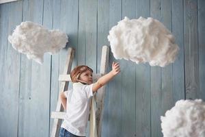 niño con sombrero de piloto de pie en la escalera en el estudio. llegar al cielo. tocar el concepto de nubes foto