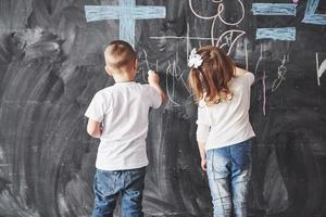 Cute little girl and boy drawing with crayon color on the wall. Works of child. Cute pupil writing on chalkboard photo