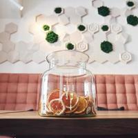 Dried candied orange, lime and lemon wheels in large glass container with contents also arranged on butcher block around jar with raw sugar and metal lid photo
