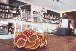 Ruedas de naranja, lima y limón confitadas secas en un recipiente de vidrio grande con el contenido también dispuesto en un bloque de carnicero alrededor de un frasco con azúcar sin refinar y tapa de metal foto