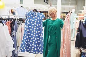 imagen de la señorita de pie en la tienda de ropa en el interior eligiendo vestidos. mirando a un lado foto