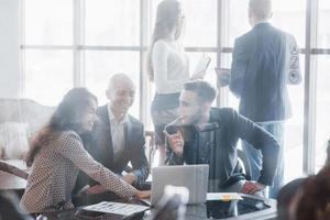 joven equipo de compañeros de trabajo haciendo una gran discusión de negocios en la moderna oficina de coworking. concepto de personas de trabajo en equipo foto