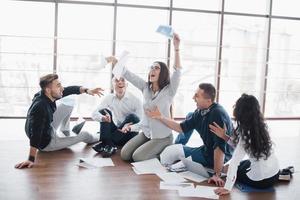 jóvenes creativos en la oficina moderna. grupo de jóvenes empresarios están trabajando junto con la computadora portátil. autónomos sentados en el suelo. logro corporativo de cooperación. concepto de trabajo en equipo foto