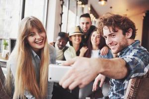 Retrato de grupo de viejos amigos alegres que se comunican entre sí, amigo posando en la cafetería, gente de estilo urbano divirtiéndose, conceptos sobre el estilo de vida de la unión de los jóvenes. wifi conectado foto