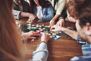 Group of creative friends sitting at wooden table. People having fun while playing board game photo