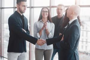 Two confident business man shaking hands during a meeting in the office, success, dealing, greeting and partner concept photo