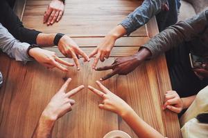 Cerrar la vista superior de los jóvenes juntando sus manos. amigos haciendo una forma de estrella con los dedos mostrando unidad y trabajo en equipo foto