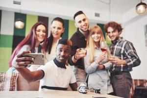 Friends having fun and making selfie at restaurant.Two boys and four girls drinking beer and eating pizza with fresh salad together. Boy with cap making selfie with his phone. All wear casual clothes photo