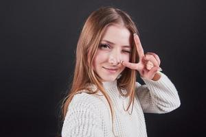 Close up portrait of beautiful young woman in white sweater and jeans, isolated on black background photo