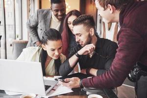 Gente de negocios multiétnica, emprendedor, negocio, concepto de pequeña empresa, mujer mostrando algo a sus compañeros de trabajo en una computadora portátil mientras se reúnen alrededor de una mesa de conferencias foto