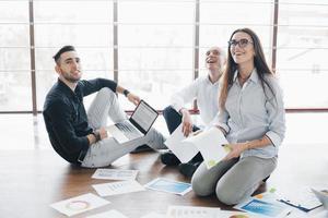 planificación de la estrategia en conjunto. equipo de negocios mirando papeles en el piso con el gerente apuntando a una idea. logro corporativo de cooperación. dibujo de diseño de planificación. concepto de trabajo en equipo foto