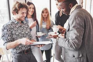 Successful young business people are talking and smiling during the coffee break in office photo