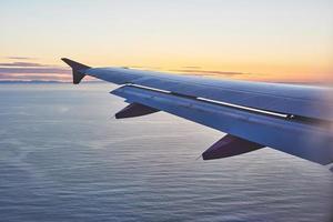 Orning amanecer con ala de un avión. foto aplicada a operadores turísticos. imagen para agregar mensaje de texto o sitio web de marco. concepto de viaje