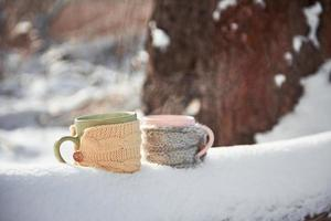 Two cups of tea on background of a winter landscape photo