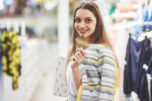 Woman in shopping. Happy woman with shopping bags and credit card enjoying in shopping. Consumerism, shopping, lifestyle concept photo