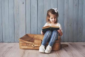 Ready to big travel. Happy little girl reading interesting book carrying a big briefcase and smiling. Travel, freedom and imagination concept photo