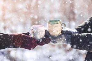 Un par de manos en guantes tomar tazas con té caliente en Winter Park foto