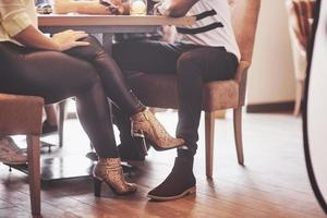 Girl flirting with a guy touching leg her foot under the table in a cafe while having fun with the friends. Flirt with your foot during lunch photo
