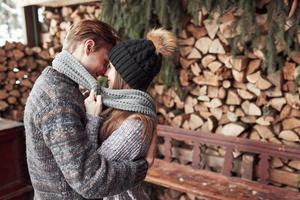 winter, vacation, couple, christmas and people concept - smiling man and woman in hats and scarf hugging over wooden country house and snow background photo
