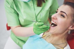 dentista curando a una paciente en la estomatología. concepto de prevención temprana e higiene bucal foto