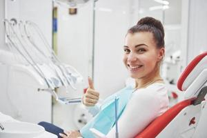 Satisfied patient showing her perfect smile after treatment in a dentist clinic photo