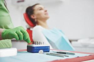 A patient in a dental clinic sits in a chair and the doctor prepares the tools for treatment photo