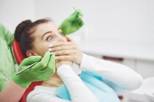 niña asustada en la oficina del dentista cubrió la boca con las manos. concepto fobia consultorio dental foto