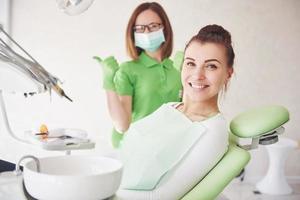 una mujer joven está satisfecha con el trabajo del dentista y levanta el pulgar foto