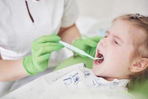 chequeo de dientes en el consultorio del dentista. Dentista examinando los dientes de las niñas en la silla del dentista foto