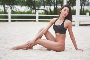 Beautiful slim luxury girl in bikini on the sand beach on a tropical island. Sexy tanned body and perfect figure photo