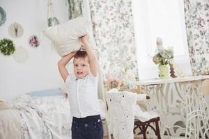 Little boy in white shirt with pillow. Pillow fight photo