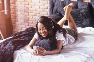 Portrait of beautiful woman waking up in her bed and looks into the phone. Check social networks, send sms. The girl is wearing a T-shirt photo