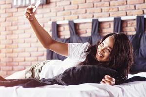 Happy beautiful african girl in sleepwear stretching smiling sitting on bed at home woke up in the morning on a sunny day photo
