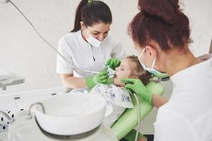 Manos de dentista pediátrico irreconocible y asistente que hace el procedimiento de examen para una niña linda sonriente sentada en una silla en el hospital foto