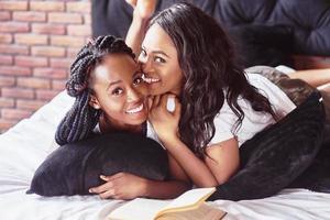 dos hermosa niña africana en ropa de dormir sonriendo sentada en la cama en casa se despertaron por la mañana en un día soleado. foto