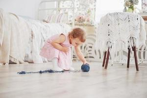Childhood concept. Baby girl in cute dress play with colored thread. White vintage childroom photo
