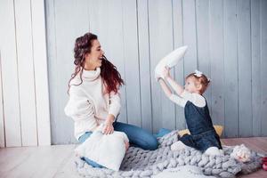 familia feliz la madre y su niña están peleando almohadas. juegos familiares felices foto