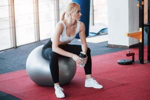 Relaxing after training. View of beautiful young woman looking away while sitting on exercise mat at gym photo