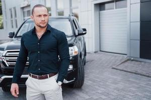 Portrait of a young bodyguard near the car. He performs dangerous work photo