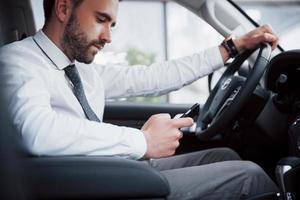 Hombre de negocios joven satisfecho mirando el teléfono móvil mientras conduce un coche foto