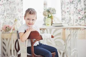 Small boy in blue trousers jeans is sitting on the wooden chair in the room. Makes homework. Back to school photo