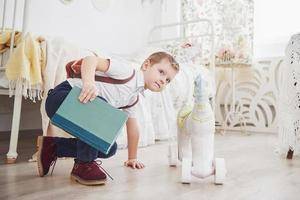 Cute little boy is going to school for the first time. Child with school bag and book. Kid makes a briefcase, child room on a background. Back to school photo