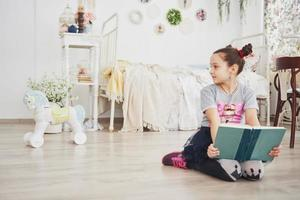 Cute little child girl reading a book in the bedroom. Kid with crown sitting on the bed near window photo