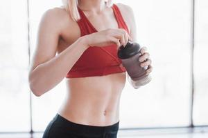Photo of attractive fitness woman in gym and holding bottle of water
