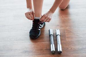 Young girl runner tying her shoelaces. Shot on floor background in fitness center photo