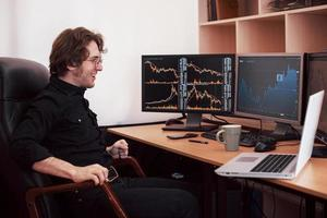 Businessmen trading stocks online. Stock broker looking at graphs, indexes and numbers on multiple computer screens. Business success concept photo