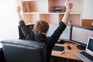 corredor de bolsa joven que estira las manos en el lugar de trabajo, primero logró un gran éxito en el mercado de valores foto